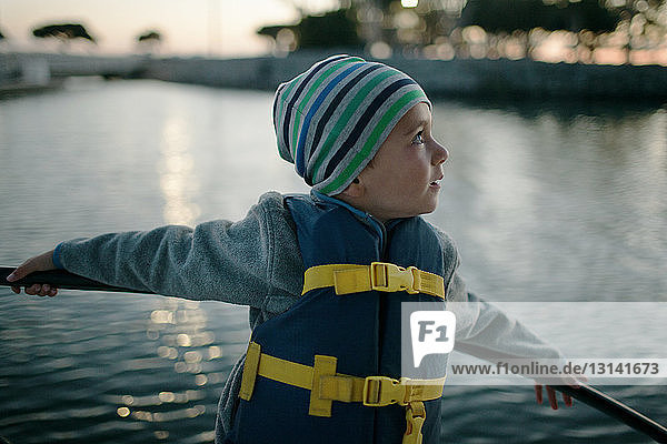 Boy looking away while standing by railing on boat