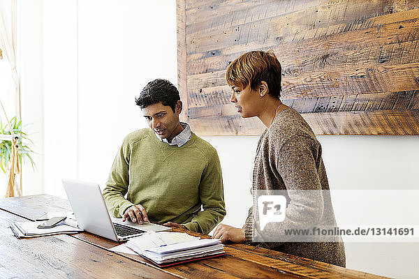 Male and female business colleagues using laptop at table in creative office