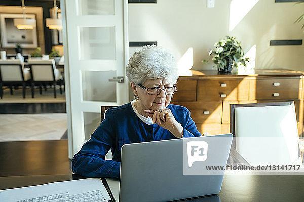 Seriöse ältere Frau  die zu Hause einen Laptop benutzt
