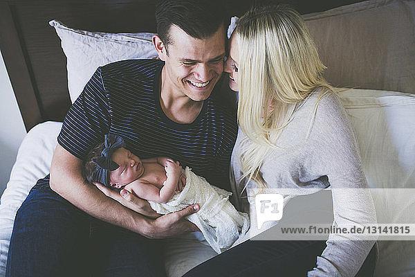 Hochwinkelansicht von glücklichen Eltern mit Tochter im Bett zu Hause