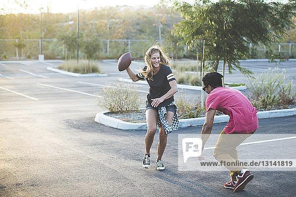 Glückliche Freunde spielen mit American Football auf dem Parkplatz