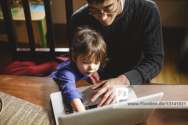 High angle view of father with daughter using laptop computer on wooden table at home