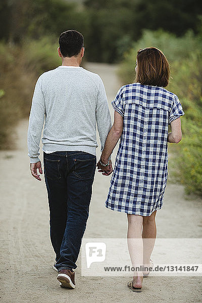 Rear view of couple holding hands while walking on dirt road