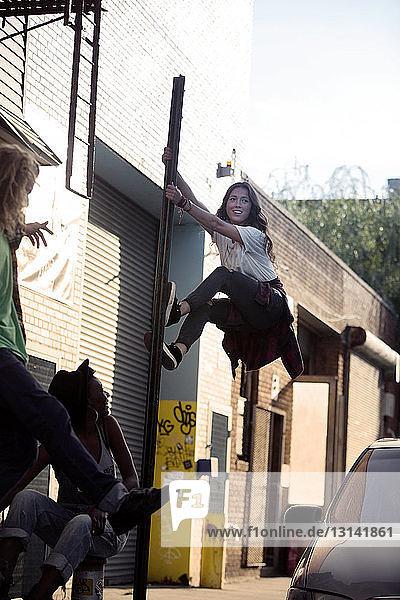 Zuversichtliche Frau klettert in der Stadt an Stange