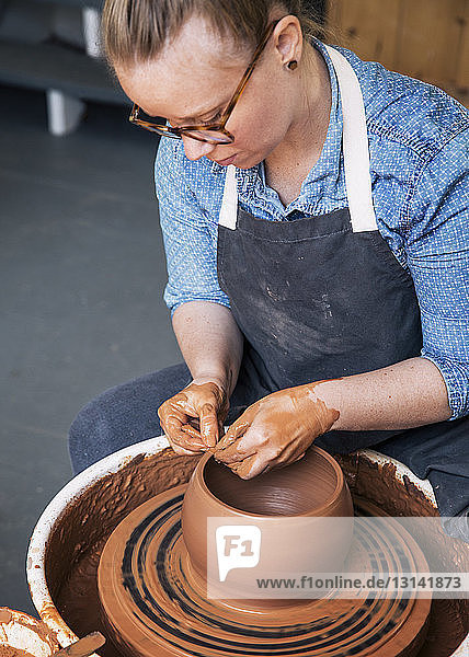Woman working on pottery wheel at workshop