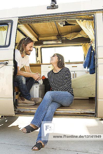 Glückliches Paar unterhält sich während des Urlaubs im Mini-Van