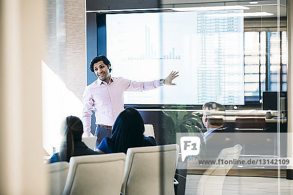 Businessman giving presentation in meeting seen through window