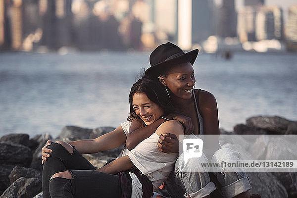 Fröhliche Freunde umarmen sich  während sie am felsigen Strand sitzen