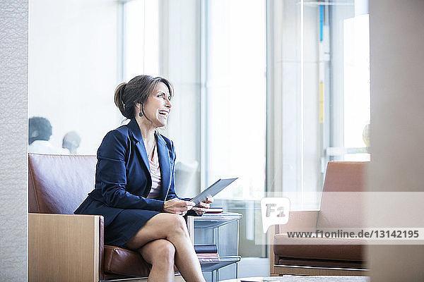 Fröhliche Geschäftsfrau hält Tablet-Computer in der Hand  während sie auf dem Sofa sitzt