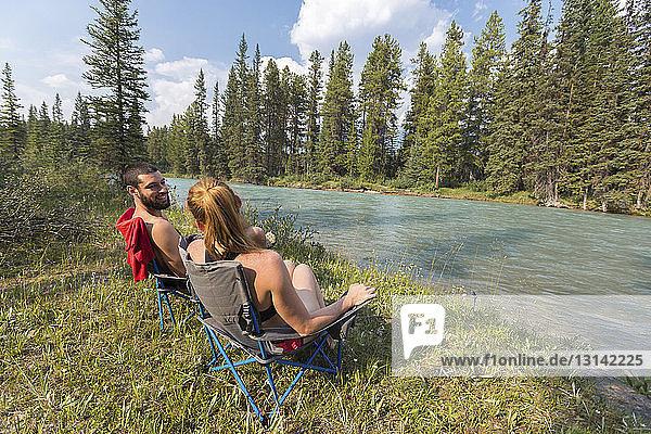 Freunde unterhalten sich  während sie auf Stühlen am Flussufer im Banff-Nationalpark sitzen