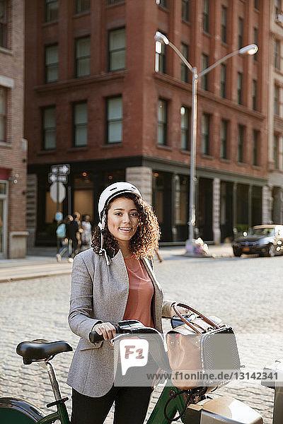 Porträt einer lächelnden Geschäftsfrau  die eine Fahrradaktie auf einem Parkplatz auf der Straße hält