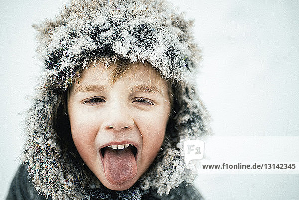 Close-up portrait of boy sticking out tongue during snowfall