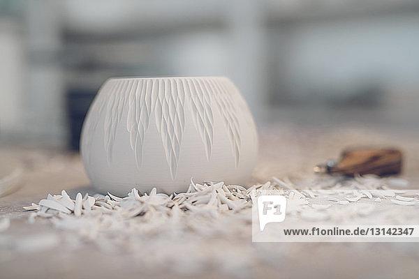 Nahaufnahme von geschnitzter Keramik auf dem Tisch in der Werkstatt Nahaufnahme von geschnitzter Keramik auf dem Tisch in der Werkstatt
