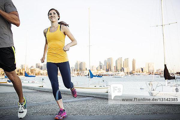 Lächelnde Sportlerin joggt mit Freundin am Pier am Hafen