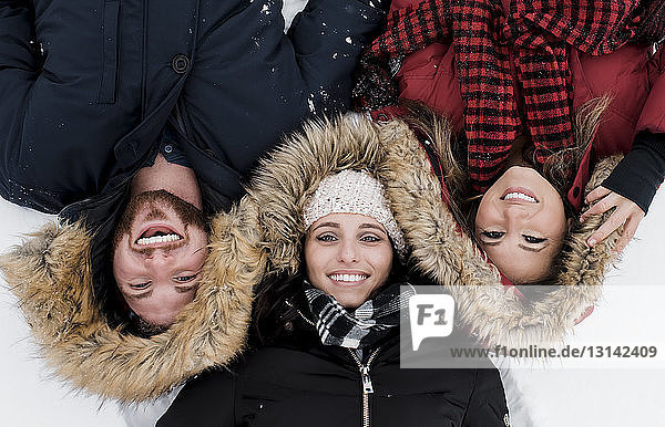 High angle portrait of smiling friends lying on snow covered field