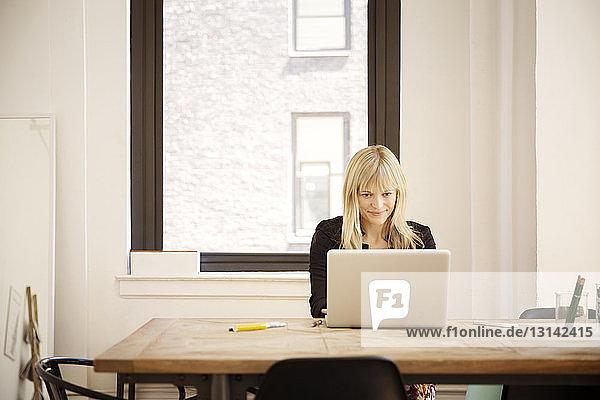 Schöne Geschäftsfrau mit Laptop am Schreibtisch im Büro