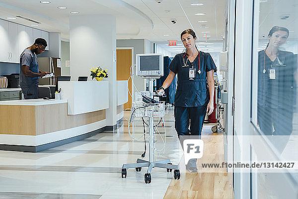 Porträt einer selbstbewussten Ärztin bei der Überwachung von Geräten  wobei die Kollegin am Krankenhausempfang steht