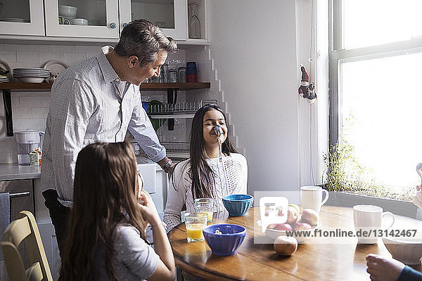 Father looking at girl balancing spoon on nose at table in kitchen