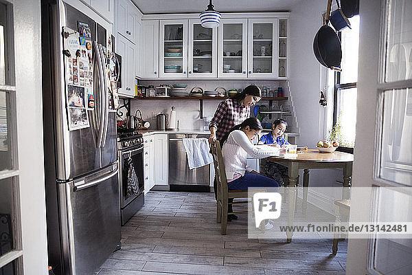 Frau hilft Töchtern beim Lernen am Tisch in der Küche