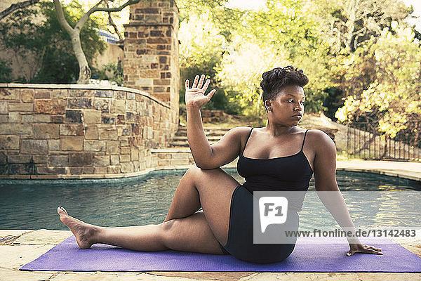 Zuversichtliche Frau macht Wirbelsäulendrehung auf der Matte am Pool