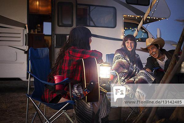 Freunde genießen beim Camping gegen Wohnmobil in der Nacht