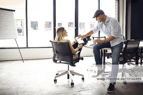 Business colleagues discussing over tablet in creative office