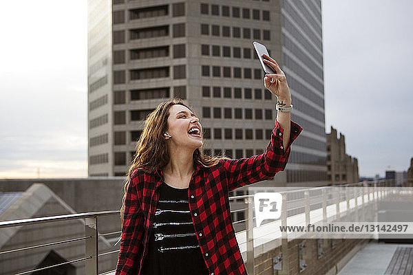 Fröhliche junge Frau  die sich beim Stehen auf der Terrasse gegen das Gebäude Selbsthilfe nimmt