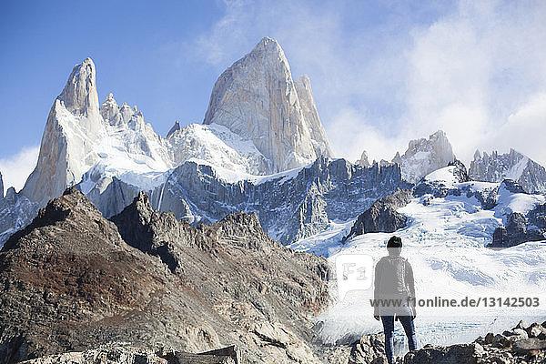 Rückansicht einer Frau  die vor schneebedeckten Bergen steht