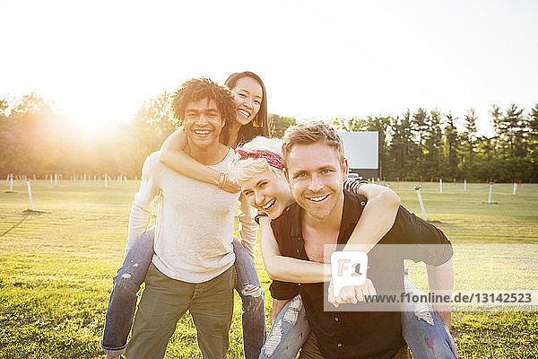 Porträt von lächelnden Männern  die Freunde auf dem Spielfeld huckepack nehmen