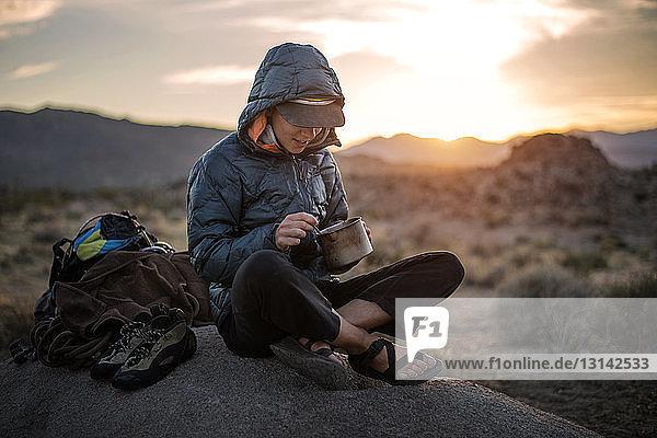 Glückliche Wanderin isst Essen  während sie auf einer Sanddüne sitzt