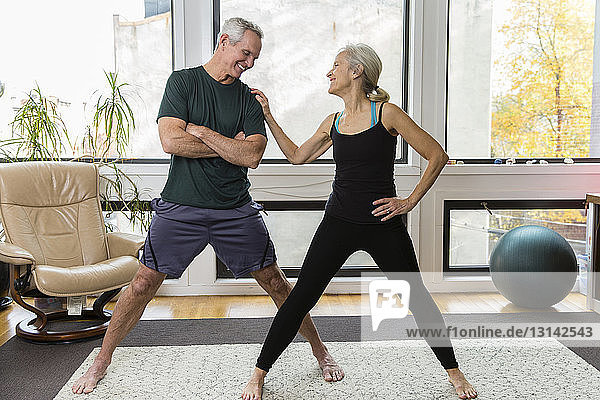 Smiling woman talking with man while exercising against windows at home