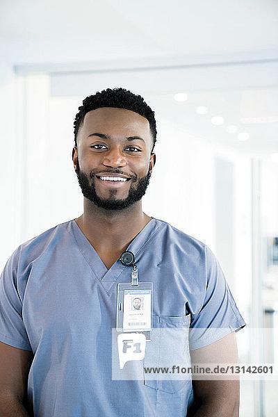 Portrait of smiling doctor standing in hospital corridor
