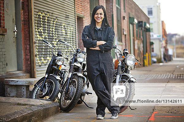 Porträt einer glücklichen Mechanikerin  die vor dem Geschäft gegen Fahrräder steht