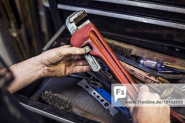 Hochwinkelansicht der Hände  die den einstellbaren Schraubenschlüssel in der Werkstatt halten