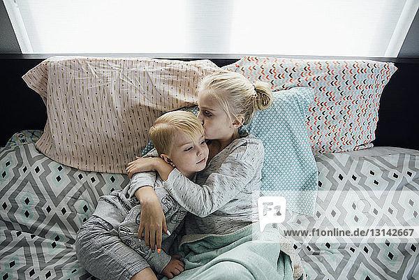 Hochwinkelaufnahme einer Schwester  die den Bruder küsst  während sie zu Hause auf dem Bett liegt
