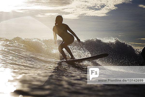 Frau surft in den Sommerferien auf dem Meer
