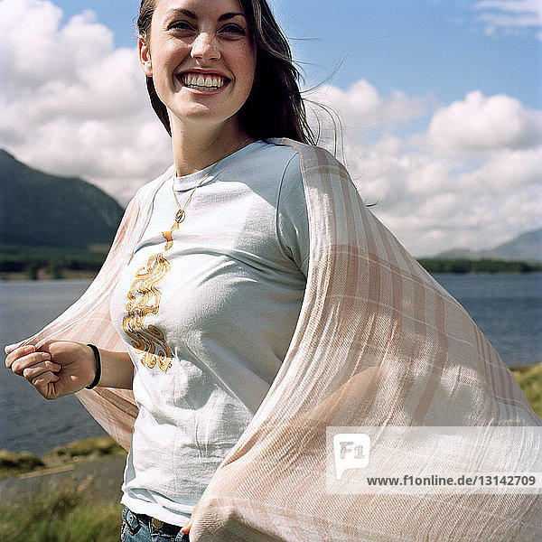 Cheerful woman holding scarf while standing on lakeshore against cloudy sky