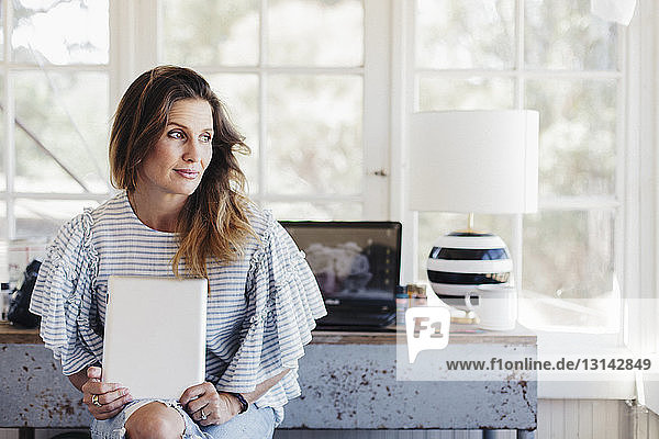 Thoughtful woman looking away while holding tablet computer in office