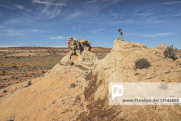 Frau in voller Länge auf Felsformation gegen den Himmel stehend