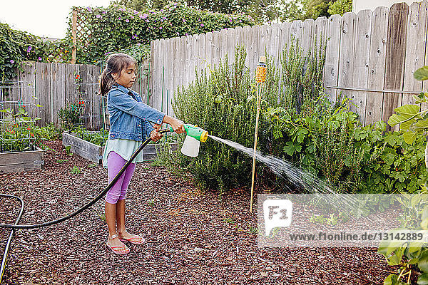 Side view of girl watering plants at backyard
