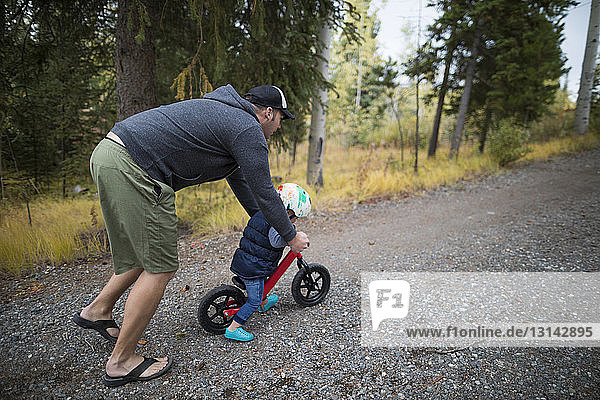 Father teaching son to ride bicycle on road