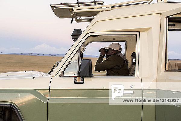 Side view of man looking through binoculars while sitting in off-road vehicle