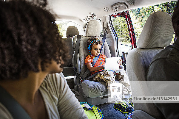 Mother looking at son using laptop computer in car
