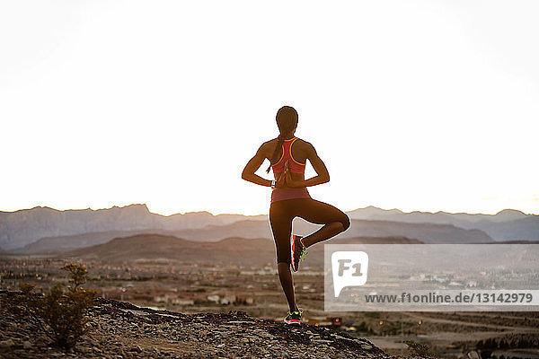 Rückansicht einer yogapraktizierenden Frau auf Landschaft vor klarem Himmel