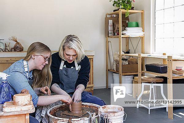 Women working on pottery wheel in workshop