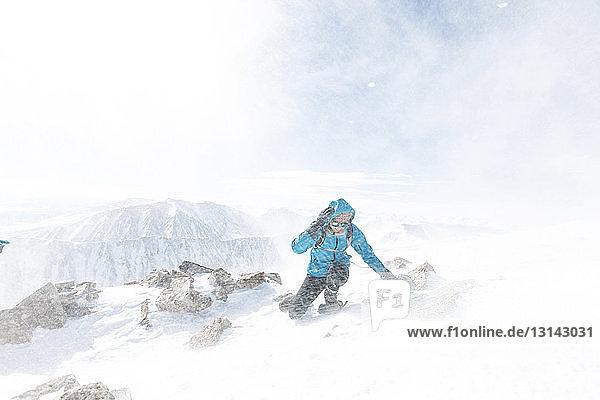 Frau auf schneebedecktem Berg während Schneesturm