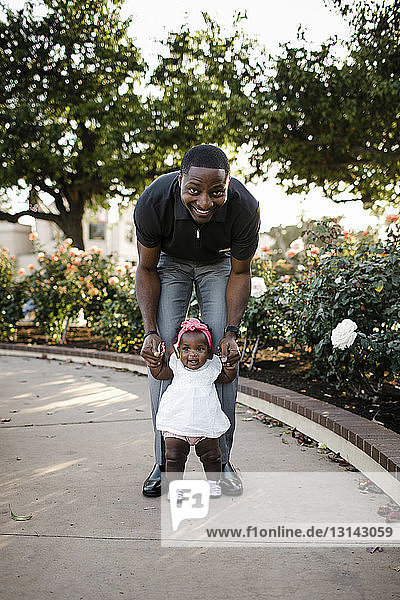 Portrait of father assisting daughter in walking on footpath at park