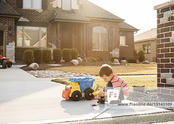 Boy playing with toy truck on driveway