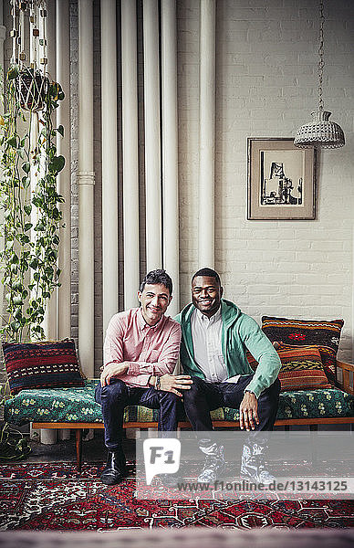 Full length portrait of happy multi-ethnic gay couple sitting on chaise longue at home