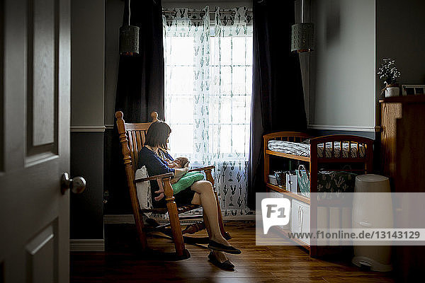 Mother breastfeeding newborn son while sitting on rocking chair seen through doorway at home